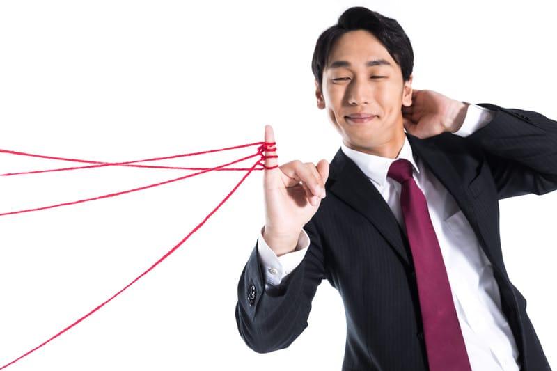 赤い糸をたくさん見つめている男性